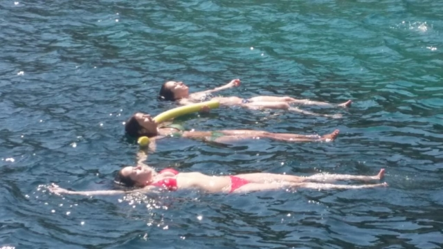 Three girls in a row floating on the sea